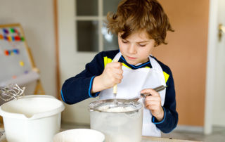 Pictures is a boy cooking in his home.