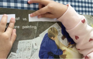 A St Gertrudes Catholic Primary School Smithfield kindy student uses two strips of paper to isolate two words within a full sentence