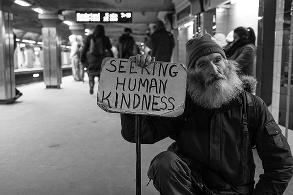 A homeless man holds a sign saying 'Seeking Human Kindness'