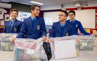 Catholic Intensive English Centre students Yoneel Marzeena, Danial Mati, Yohan Al-Lalo and Noel Jamil receiving donated education packs.