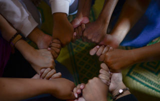 People holding hands in a circle formation