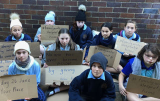 St Patrick's Catholic Primary School Sutherland students with placards highlighting the importance of helping people who are experiencing or at risk of homeless