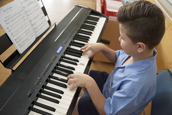 A primary school student plays the piano