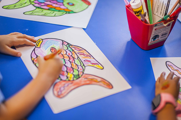 A small child works on a fish drawing