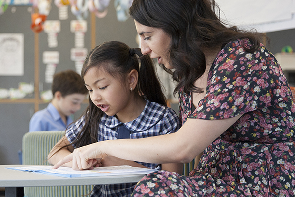 A teacher helps a primary school student with her school work