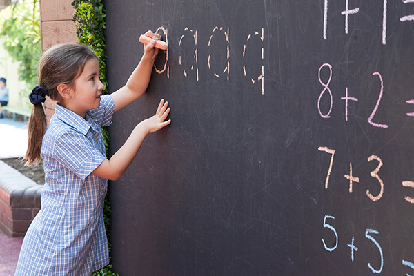 A young girl in school uniform writes words on a chalk board