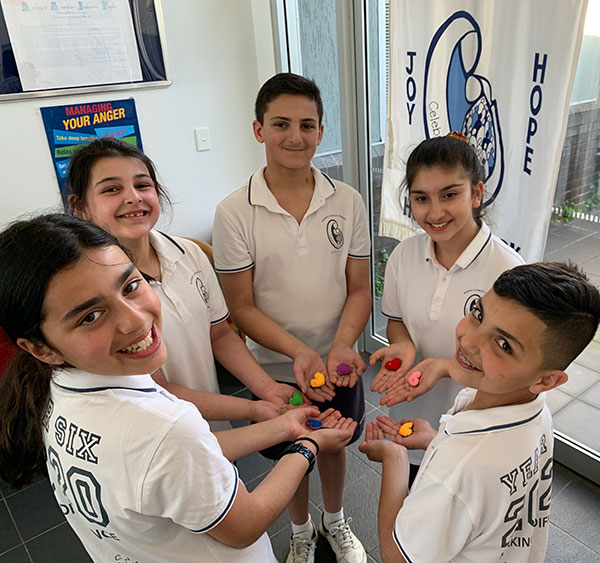 Marion Catholic Primary School students hold felt hearts they have made to donate