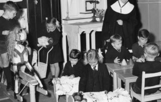 Sister Aidan Hayes teaches St James' kindy students in 1956