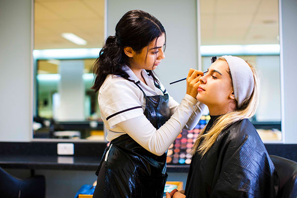 A Southern Cross Catholic College Burwood Beauty Services student applies make-up to a student 'customer'