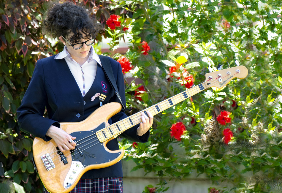 Gala Alemany Traconis plays a bass guitar