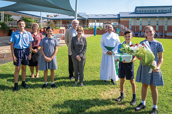 Holy Spirit Carnes Hill school captains, Mia Yenco and Matthew Sanasi, present the governor of NSW with flowers and a gift