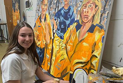 Bronte Stark from De La Salle Cronulla in front of her painting of firefighters