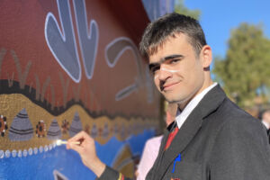 A Marist College Eastwood male students helps create an Indigenous mural with Wandana artists
