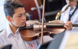 Trinity College Auburn Regents Park male student plays violin as part of Amadeus Music Education Program