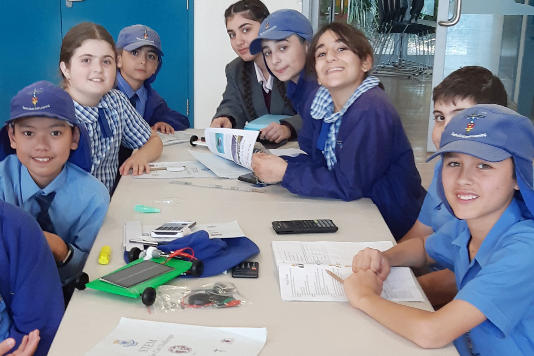 Smiling Sydney Catholic Schools students build solar cars together