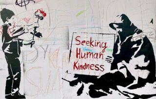 Boy hands flower to man holding sign reading 'Seeking Human Kindness' - Photo by Bekky Bekks on Unsplash