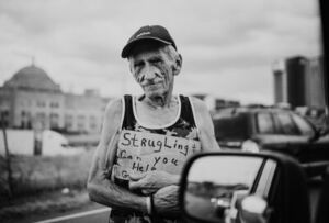 Homeless man holds sign that reads 'Struggling Can you Help' - Photo by Zoe Vandewater by Unsplash