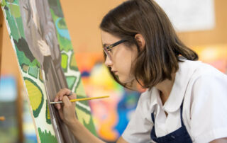 A secondary student is painting
