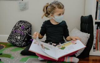 Student reading a book wearing a COVID-19 mask