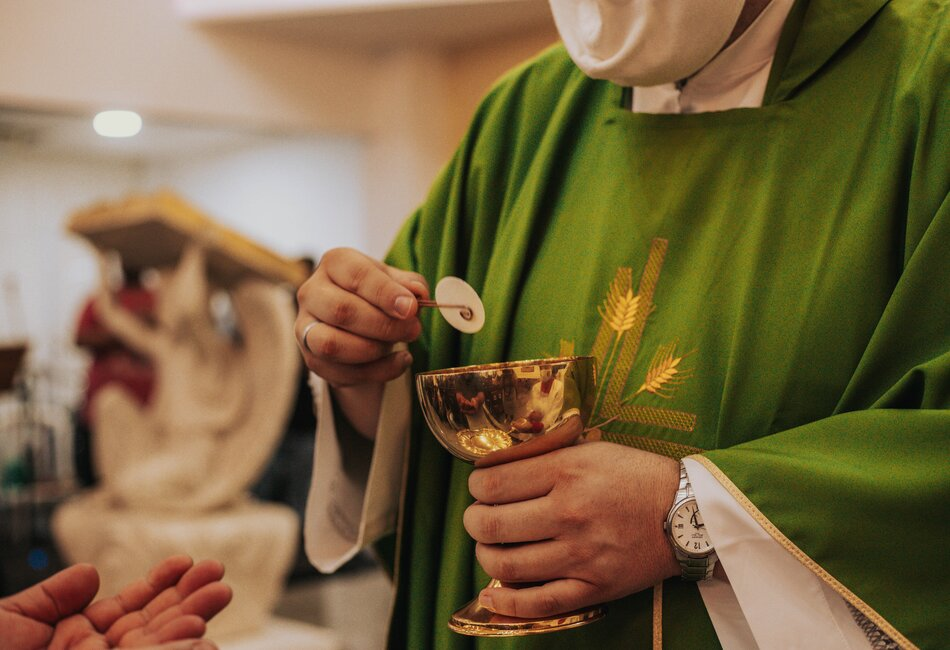Priest presenting the Consecrated host to a parishioner in COVID times