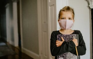 A girl wearing a COVID mask holding a book